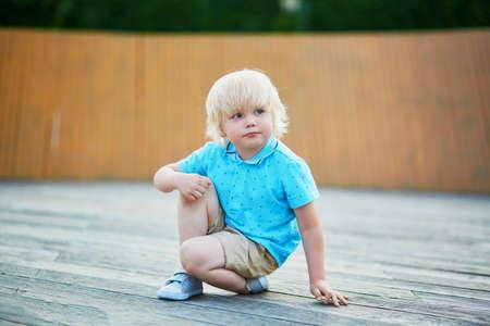 놀이터에서 자신의 고랑에 쪼그리고 앉아있는 귀여운 꼬마