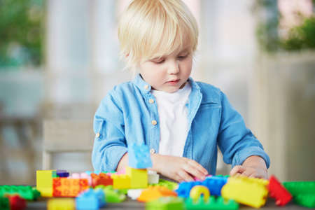 Adorable little boy playing with colorful plastic construction blocks at home, in kindergaten or preschool. Creative games for kids