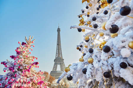 Decorated Christmas trees covered with snow near the Eiffel tower in Paris, France