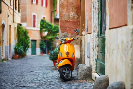 Old fashioned orange motorbike on a street of Trastevere district, Rome Imagens