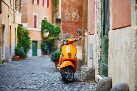 Old fashioned orange motorbike on a street of Trastevere district, Rome Stockfoto