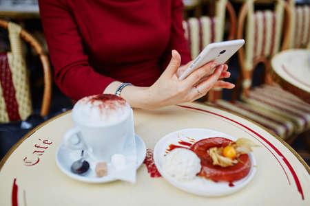 Primer plano de manos de mujer con teléfono móvil, taza de café y pastel en el café al aire libre parisino Foto de archivo - 87043850