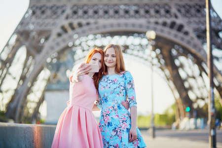 Two friends taking selfie near the Eiffel tower in Paris, France