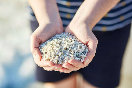 Girl with handful of small white pebbles from rice beach Is Arutas in Sardinia, Italy