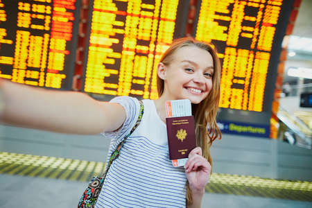 Beautiful young tourist girl in international airport, taking funny selfie with passport and boarding pass near flight information board