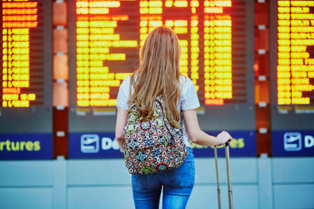 Beautiful young tourist girl with backpack and carry on luggage in international airport, near flight information board Фото со стока