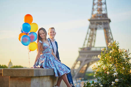 Loving couple with bunch of colorful balloons kissing near the Eiffel tower in Paris, France