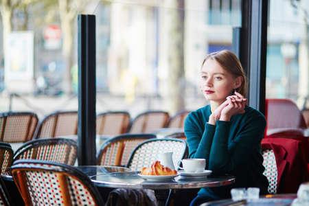 Elegant French woman drinking coffee in Parisian cafe near the window
