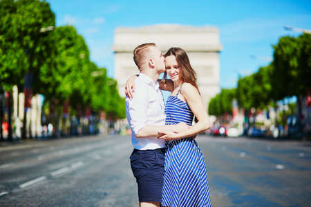 Couple kissing in front of Triumphal arch in Paris, France