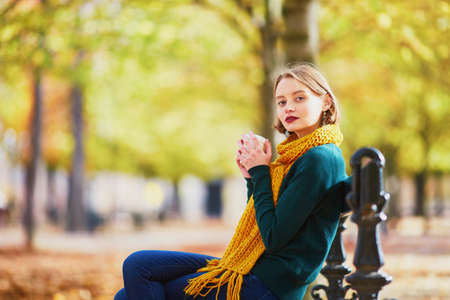 Happy young girl in yellow scarf with coffee to go walking in autumn park on a bright fall day Stock Photo