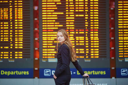 Young elegant business woman with hand luggage in international airport terminal, looking at information board, checking her flight. Cabin crew member with suitcase