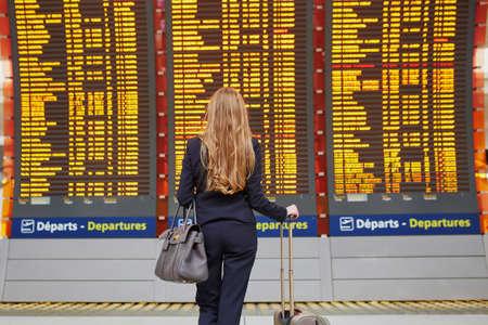 若いエレガントなビジネスの彼女のフライトをチェック情報板を見て国際空港ターミナルで手荷物を持つ女性。スーツケースと機内乗務員