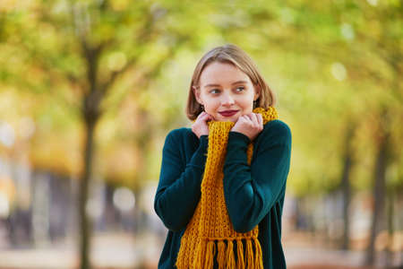 Happy young girl in yellow scarf in autumn park on a bright fall day