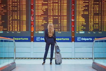 Junge elegante Geschäftsfrau mit Handgepäck im internationalen Flughafenabfertigungsgebäude, das Informationsbrett betrachtend und überprüfen ihren Flug. Kabinenpersonal mit Koffer Standard-Bild