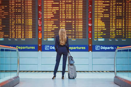 Mulher de negócio elegante nova com bagagem de mão no terminal de aeroporto internacional, olhando a placa da informação, verific seu voo. Membro da tripulação de cabine com mala Foto de archivo