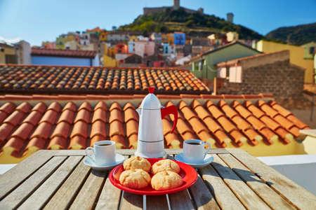 Coffemaker, twee kopjes verse espressokoffie en traditionele Italiaanse zoetigheden op een tafel met restaurant, café of terras met uitzicht op het dorp Bosa, Sardinië, Italië
