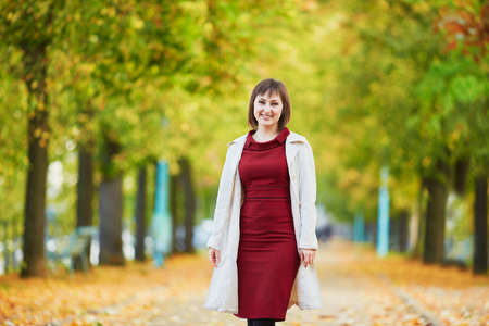 Beautiful young woman walking in Paris on a bright fall day