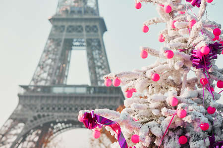 Decorated Christmas tree covered with snow near the Eiffel tower in Paris, France