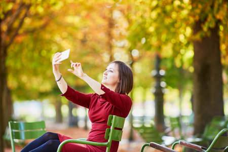 Beautiful young woman in Paris on a bright fall day, taking selfie in Tuileries garden
