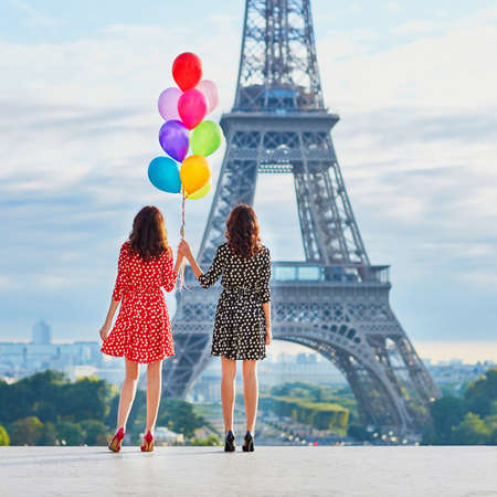Twin sisters with bunch of colorful balloons near the Eiffel tower in Paris. Tourists enjoying their vacation in France. Romantic date or traveling couple concept
