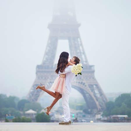 パリのエッフェル塔の近くに白いバラを持つ幸せなカップル。フランスでの休暇を楽しむ観光客。ロマンチックなデートや旅行カップルの概念