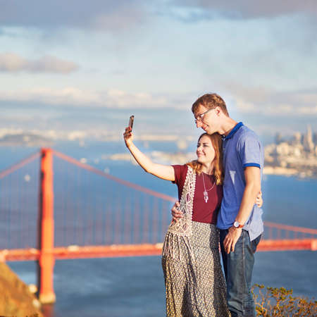 Romantic loving couple making selfie in San Francisco, California, USA. Golden gate bridge in the background