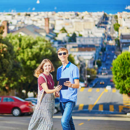 Romantic couple of tourists using tablet and planning their itinerary in San Francisco, California, USA Stock Photo