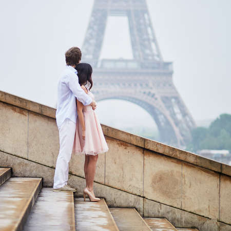 Happy couple near the Eiffel tower in Paris. Tourists enjoying their vacation in France. Romantic date or traveling couple concept