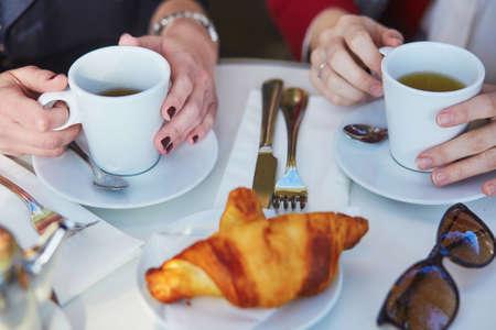 パリの屋外カフェで2人の女の子がクロワッサンとコーヒーを飲んでいます。コーヒーカップで女性の手のクローズアップ。友情の概念