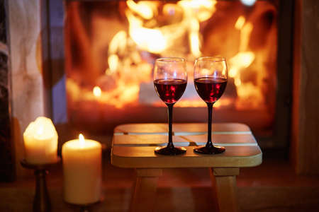 Two glasses of red wine near fireplace with many candles. Cozy romantic evening for couple or Christmas celebration concept