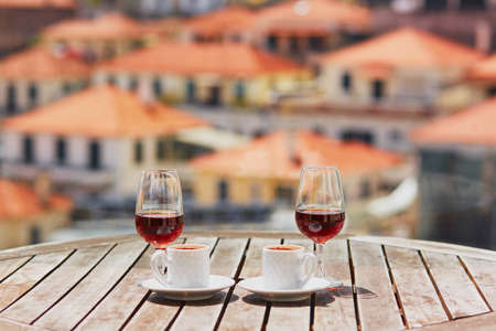 Two glasses of Madeira wine and two cups of fresh espresso coffee in street cafe with view to Funchal town, Madeira, Portugal 스톡 콘텐츠