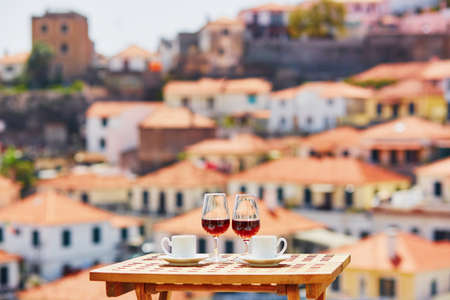Two glasses of Madeira wine and two cups of fresh espresso coffee in street cafe with view to Funchal town, Madeira, Portugal Banco de Imagens