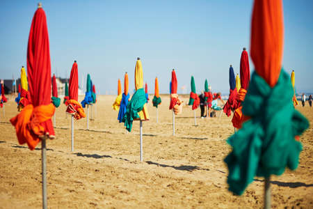 Many colorful umbrellas on the sand beach of Deauville, Normandy, France
