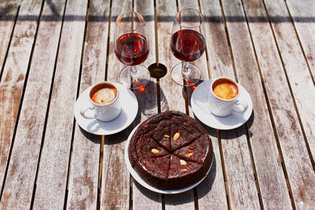 Two glasses of Madeira wine, two cups of fresh espresso coffee and traditional Portuguese honey and nut dessert bolo de mel in cafe