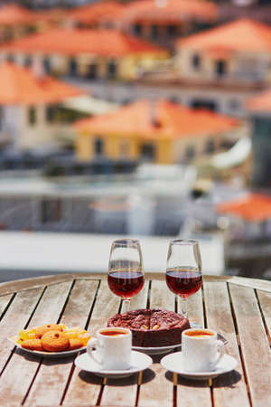 Two glasses of Madeira wine, two cups of fresh espresso coffee and traditional Portuguese honey and nut dessert bolo de mel in cafe with view to Funchal town, Madeira, Portugal Banco de Imagens - 91289406