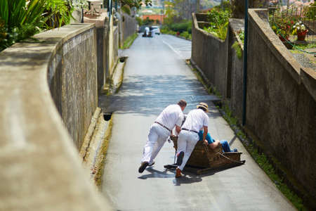 Famous fun tourist activity in Funchal, Madeira island, Portugal. Toboggan riders pushing wooden sledge with tourists downhill with high speed