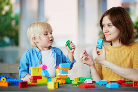 Young mother playing colorful construction blocks with her son. Quality family time. Creative games for little kids