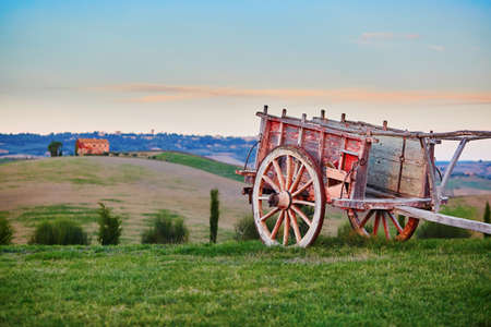 Scenic Tuscan landscape with cart, beautiful fields, meadows and hills. San Quirico dOrcia, Tuscany, Italy