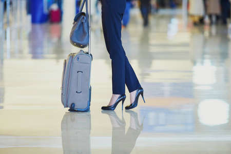 Elegant business woman with hand luggage in international airport terminal. Cabin crew member with suitcase. Unrecognizable person, closeup of legs and high heels shoes