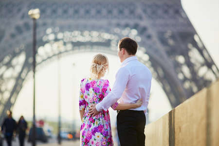 Beautiful romantic couple looking at the Eiffel tower in Paris, France. Tourism and vacation concept