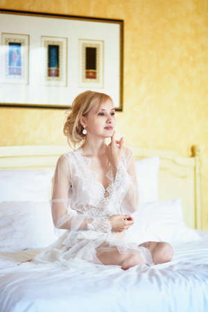 Beautiful young woman in elegant lace rest gown sitting on bed at early morning