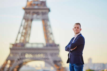 Handsome young man near the Eiffel tower in Paris Stock Photo