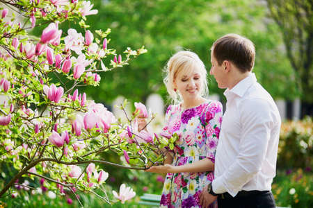 Beautiful romantic couple under blooming magnolia tree on a spring day
