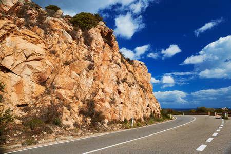 Red rocks and asphalt road on Emerald Coast, Sardinia, Italy Stock fotó