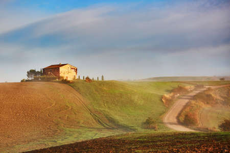Scenic Tuscan landscape with beautiful fields, meadows and hills with morning fogs. San Quirico d'Orcia, Tuscany, Italy Stock Photo - 93980922