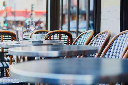 フランス・パリの屋外カフェでコーヒーカップとコップの水を飲む