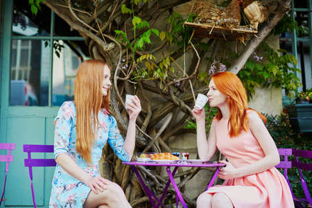 Two Parisian women drinking coffee together in an outdoor cafe with wisteria in full bloom. Paris, France Stock Photo
