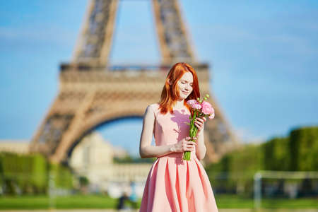 Beautiful young girl with flowers in front of the Eiffel tower Imagens