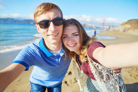 Romantic loving couple taking selfie in San Francisco, California, USA. Golden gate bridge in the background