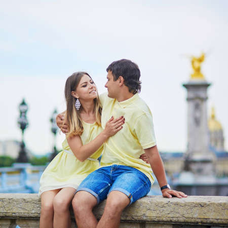 Romantic dating couple of tourist in Paris, on the famous Alexandre III bridge over the Seine